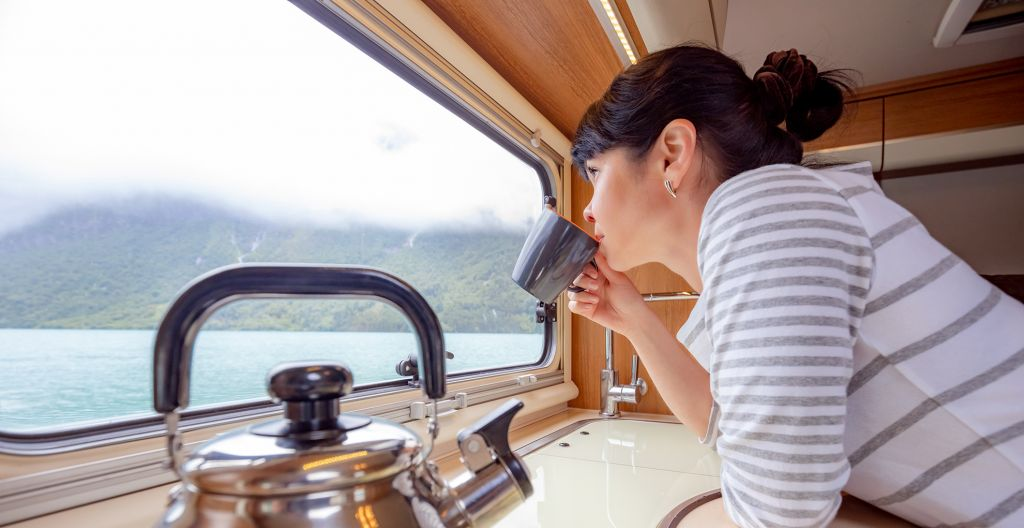 nainen katsoo asuntoauton ikkunasta ulos ja juo kahvia