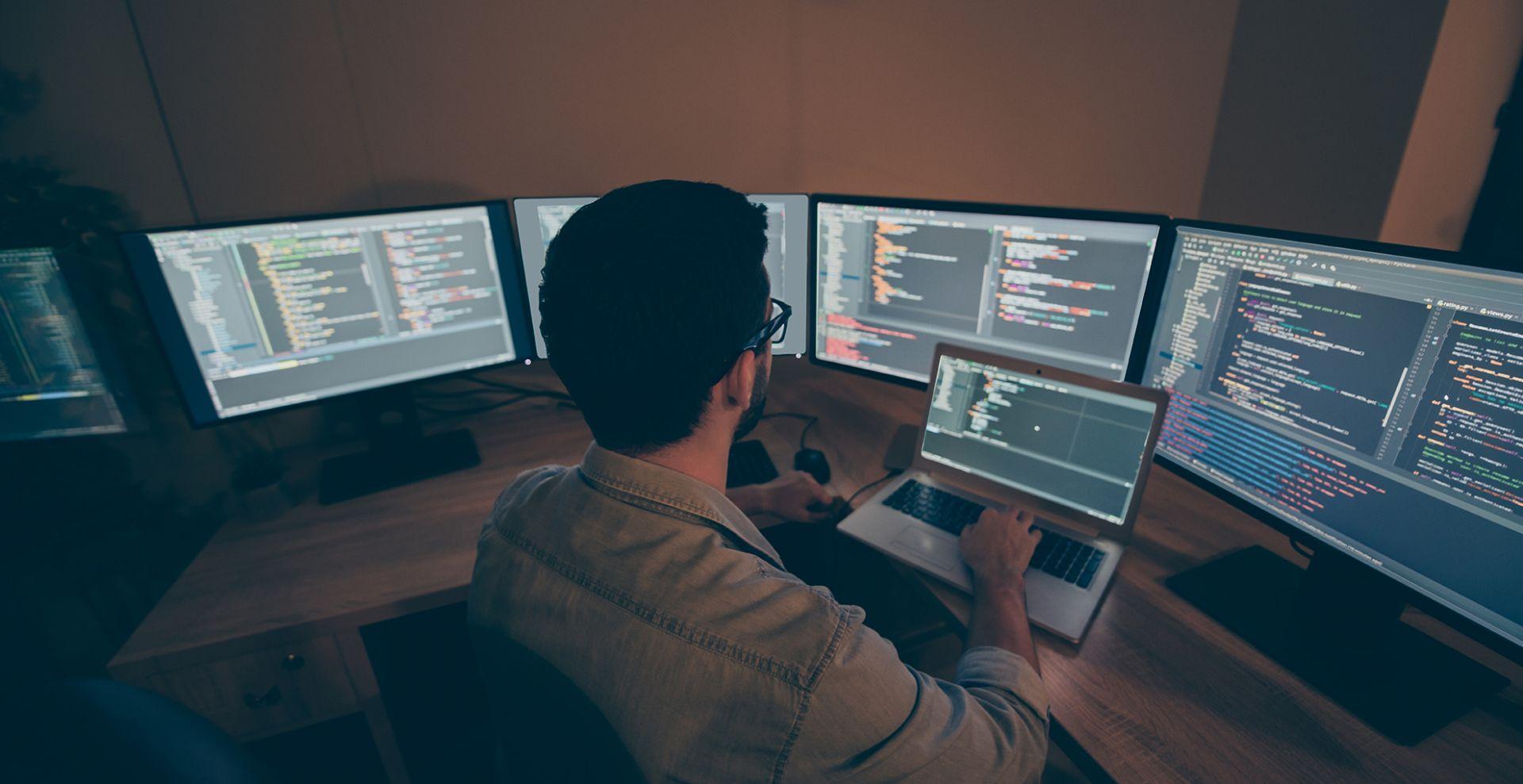 mies useiden tietokoneen näyttöjen keskellä