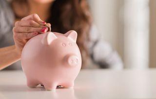 nainen laittaa kolikon posliiniseen säästöpossuun