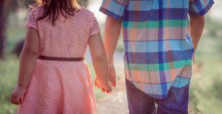 lapset kävelemässä käsi kädessä