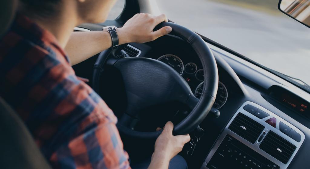 Ruutupaita ajaa autoa, ratti ja kädet
