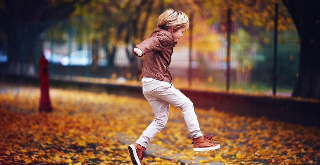 poika hyppää syksyn lehtien joukossa