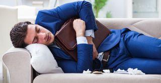 Pukuun pukeutunut mies makaa sairaana sohvalla.