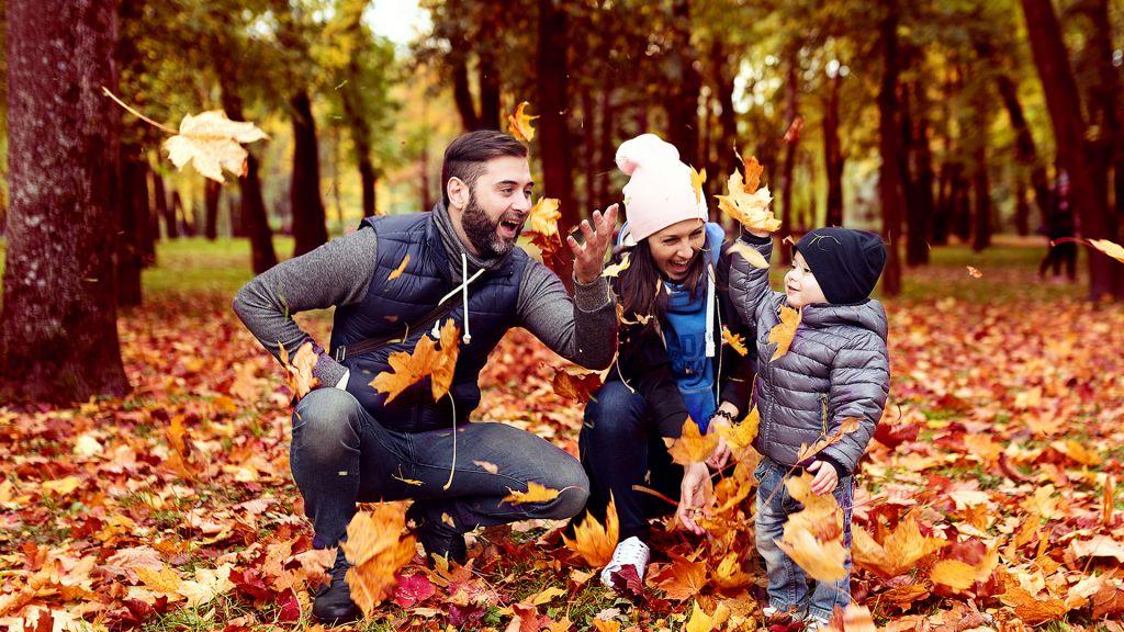 perhe leikkii oranssien lehtien joukossa