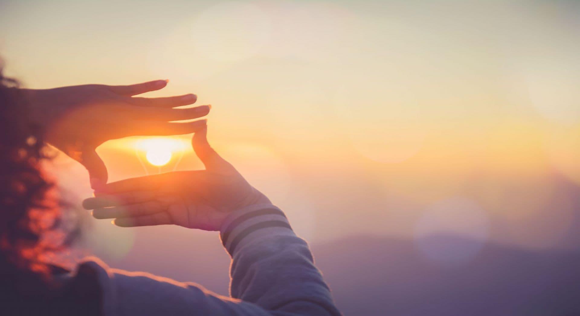 Kuvituskuva, ihminen tekee käsistään kehykset auringolle