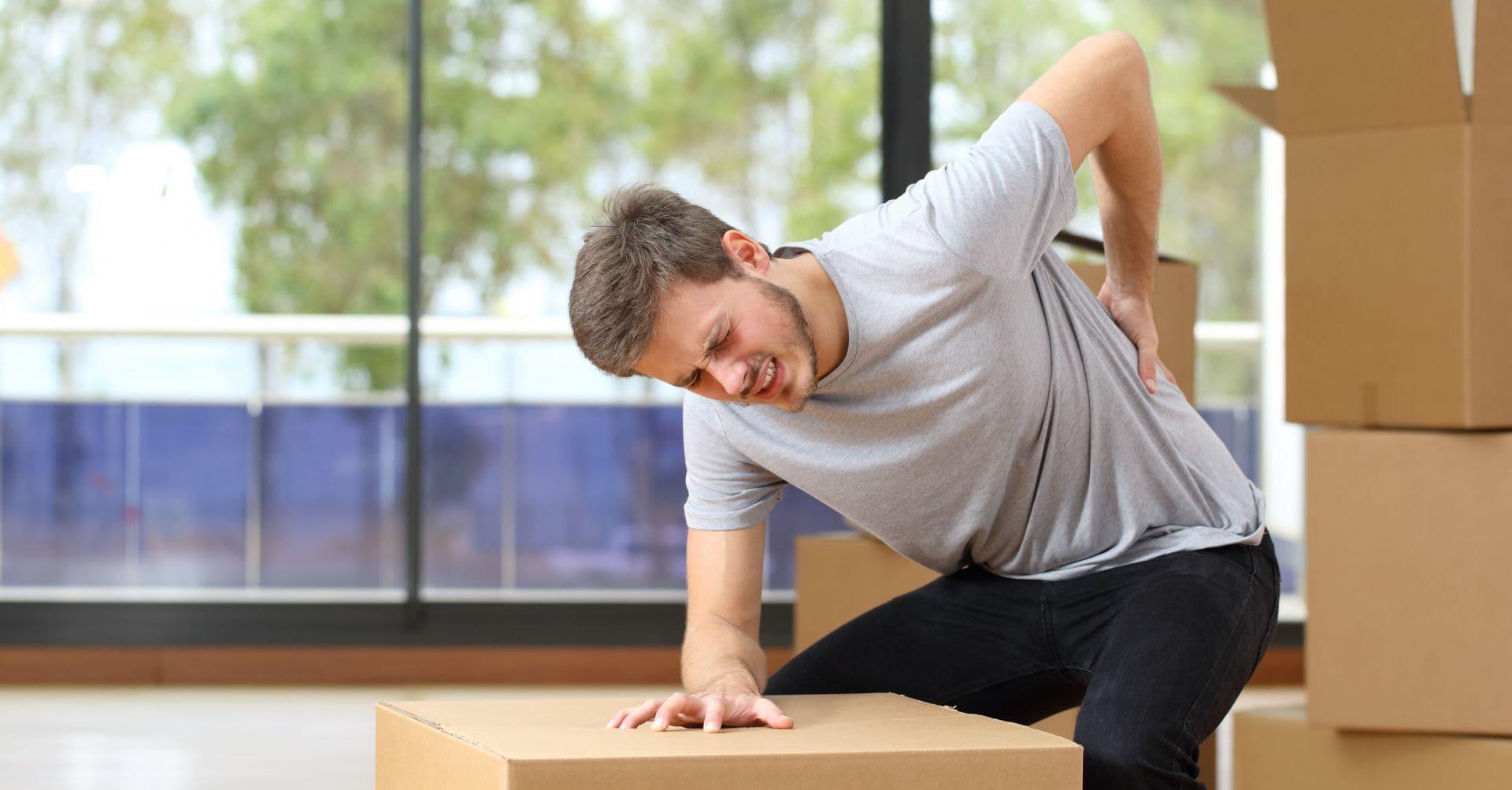 Mies satuttaa selkänsä nostaessaan painavaa laatikkoa.